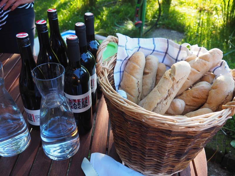 Weinflaschen und ein Korb voll frischen Baguettes auf einem Tisch